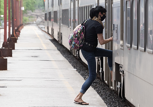 Photo of a woman wearing a mask boarding an exo train